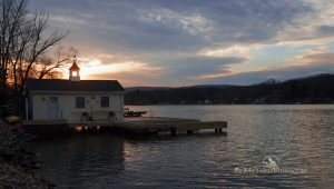 Harveys Lake Photography featuring an image of the sun sinking slowly behind a boathouse.