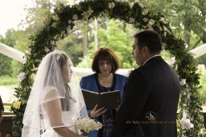 Bride and groom recite their vows under floral arch